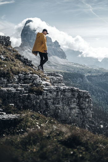 Man standing in the dolomites with a view of the mountain tops of tre cime in italy