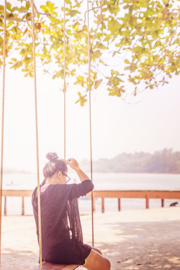 Woman sitting on swing at beach during summer