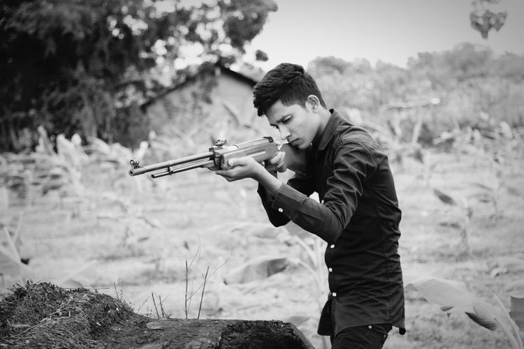 Young man aiming with rifle while standing at farm