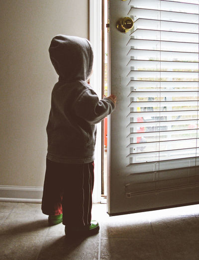 Rear view of boy looking through door at home