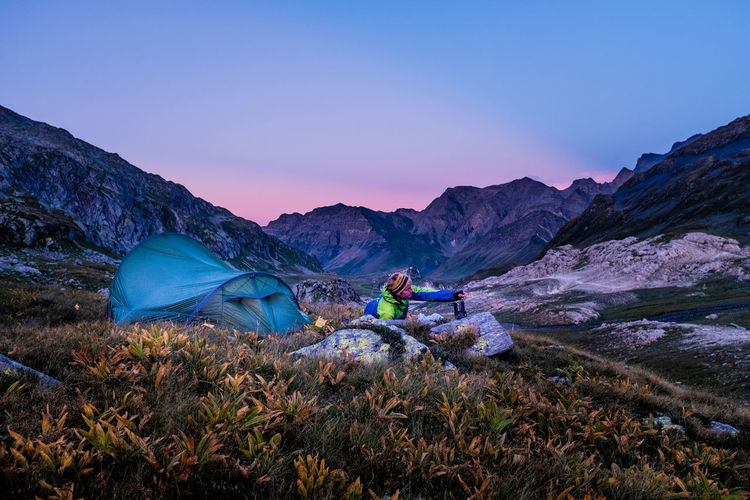 Man on land by tent against mountains and sky during sunset