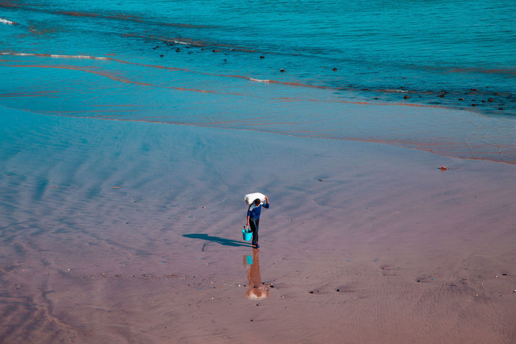 High angle view of man carrying sack on shoulders while walking on shore of beach