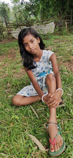 Full length of girl sitting on field
