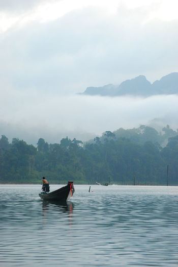Man on longtail boat in lake against cloudy sky