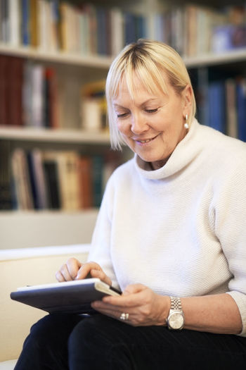 Mid adult woman using mobile phone while sitting on book