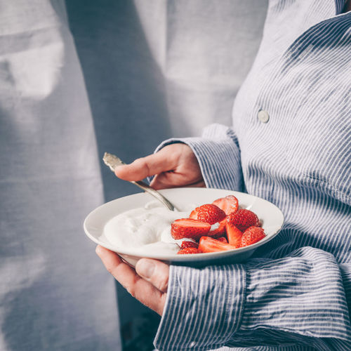 Midsection of man holding ice cream in bowl