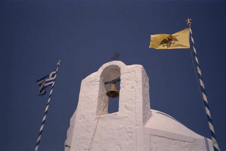 Low angle view of greek flag and bell tower against clear sky