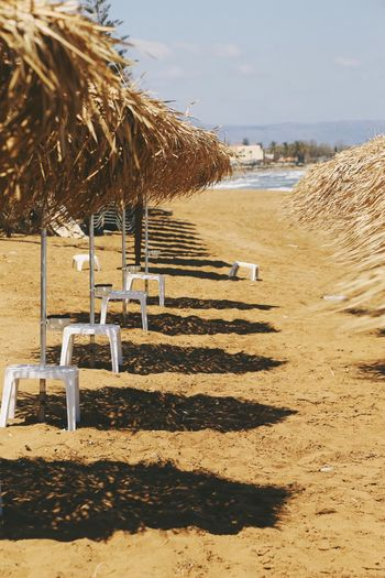 Close-up of thatched roof umbrellas at beach against sky