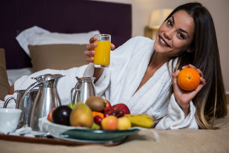Portrait of smiling beautiful woman holding drink and fruit while lying on bed at hotel