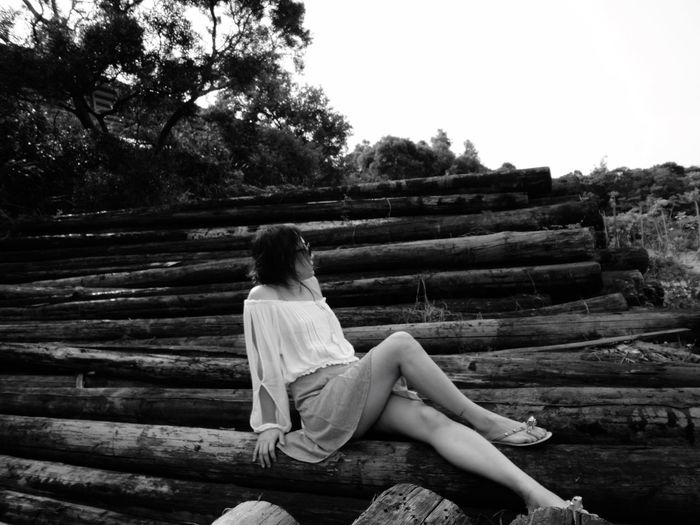 Woman relaxing on pile of wooden logs