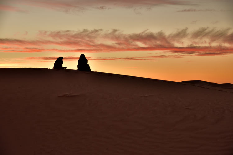 Beduines Enjoy off a Dune The Sunset . In Memory off a Fantastic Desert Trip in Morocco, I Show some Pictures. Sky Sunset Cloud - Sky Scenics - Nature Orange Color Beauty In Nature Nature Land Silhouette Real People Tranquil Scene Landscape Tranquility Unrecognizable Person Standing Idyllic Togetherness Two People Outdoors Desert Arid Climate Climate Romantic Desert Beauty Desert Atmospheric Mood Gorgeous Travel Photography Orange Sky Journey Travel people and places Nikon Nikon Photography Sand Dune Oriental Enjoying Life Silence Of Nature Holiday Moments