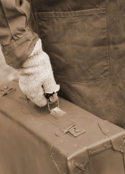 Midsection of man holding suitcase