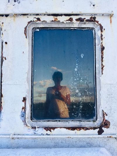 Woman reflecting on window of boat