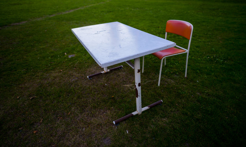 Empty chair and table on field