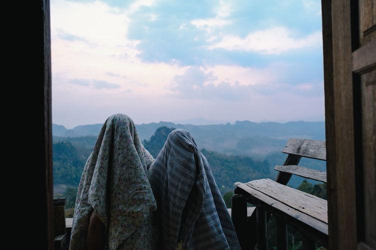 People covered in blanket standing against sky