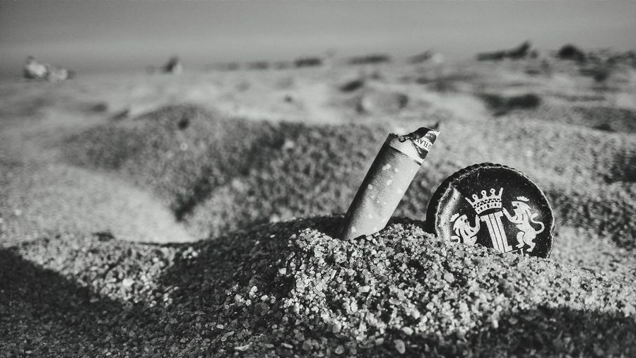 Close-up of cigarette butt on sand