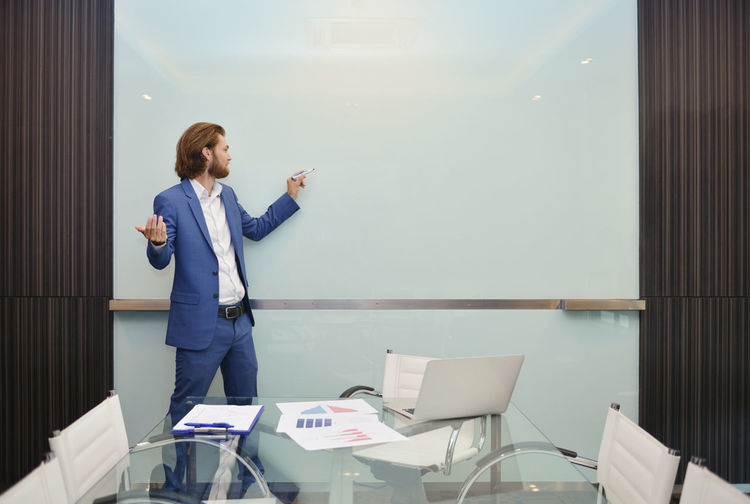 Businessman writing on whiteboard in conference room