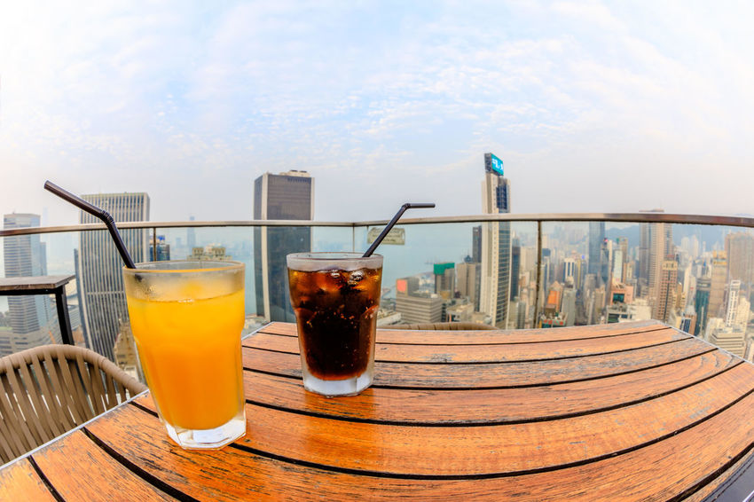 Hong Kong, China - January 1, 2016: aerial view of city skyline and cocktail from the top of The Hennessy in Wan Chai, a modern skybar in the city. HongKong Hong Kong City Hong Kong Sunset Skyline Night Cityscape Business Aerial View Light Show Laser Show Skyscraper Victoria Harbor Panorama Drink Refreshment Food And Drink Glass Drinking Glass Household Equipment Table Drinking Straw Freshness Straw No People Still Life Sky Architecture Railing Food Wood - Material Day Cold Temperature Close-up
