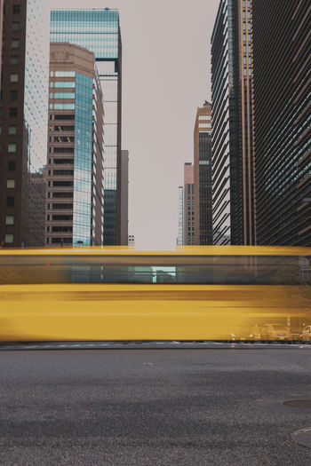 Blurred motion of bus against buildings in city