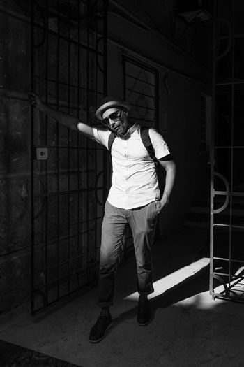 Ready to go. Adult Black And White Black Background Casual Clothing Contrast Copy Space Doorway Fashion Gate Latin America Leaning Man People Pose Shades Standing Sunglasses The Portraitist - 2017 EyeEm Awards The Street Photographer - 2017 EyeEm Awards Tourist Travel Urban Connected By Travel Stories From The City This Is Latin America