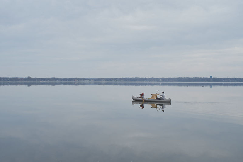 Man on boat at lake against sky