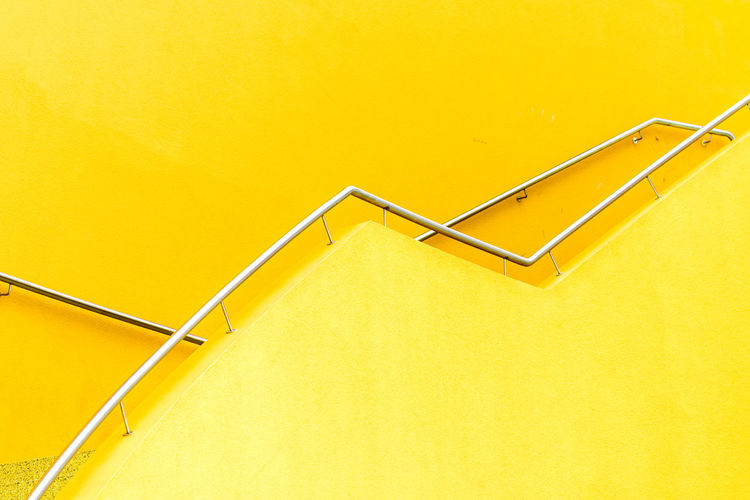 Low Angle View Of Railing On Yellow Wall
