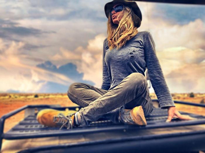 Full length of woman sitting on car roof against cloudy sky