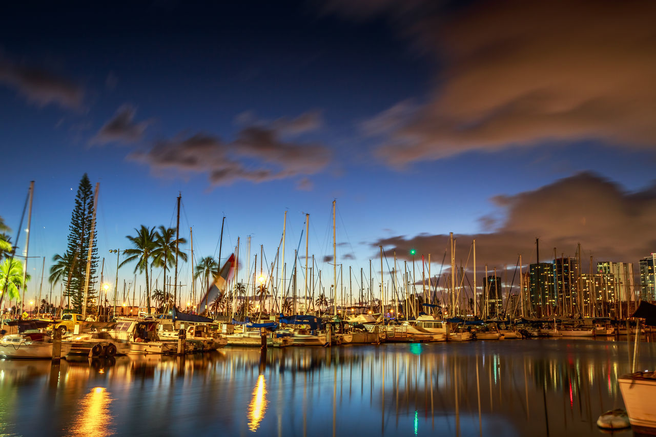 sky, water, nautical vessel, reflection, moored, harbor, cloud - sky, waterfront, mast, marina, no people, built structure, travel destinations, nature, yacht, sailboat, architecture, outdoors, sea, palm tree, building exterior, beauty in nature, day, city