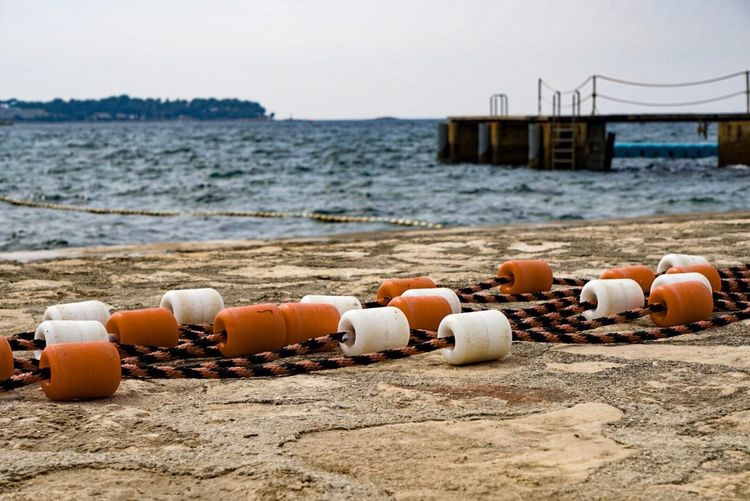 Close-up of buoys at beach against clear sky
