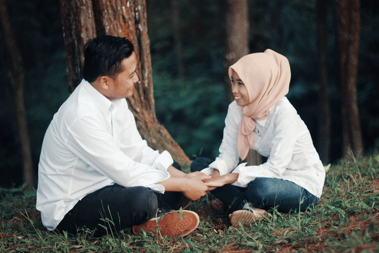 Romantic Smiling Couple Holding Hands While Sitting On Field Against Trees In Forest