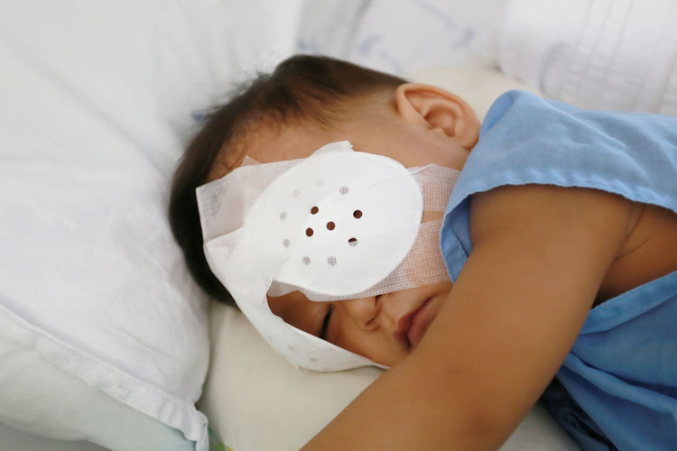 Cute boy with bandage on eye resting on bed