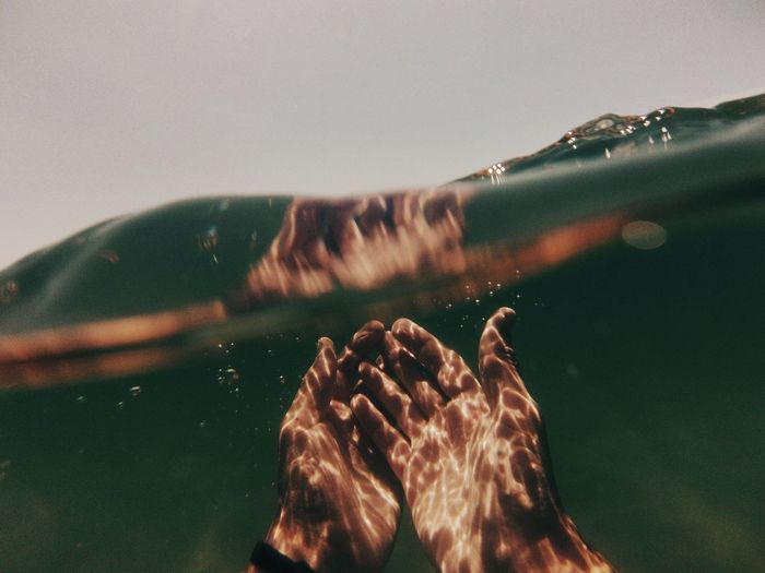 Sunlight Falling On Cropped Hands In Sea