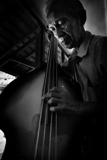 Close-Up Of Senior Man Playing Cello