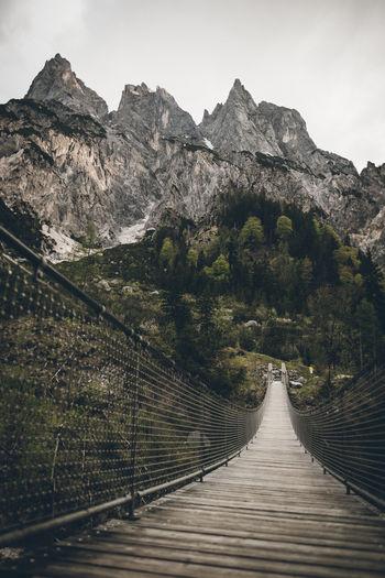 Footbridge amidst mountains against sky