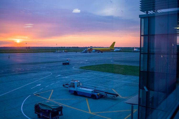 Sunset Transportation Airport Sky Mode Of Transportation Airport Runway Airplane Air Vehicle Cloud - Sky Runway Travel Orange Color Nature Commercial Airplane Public Transportation High Angle View No People Window Architecture Passenger Boarding Bridge Aerospace Industry Leaving Airport Terminal