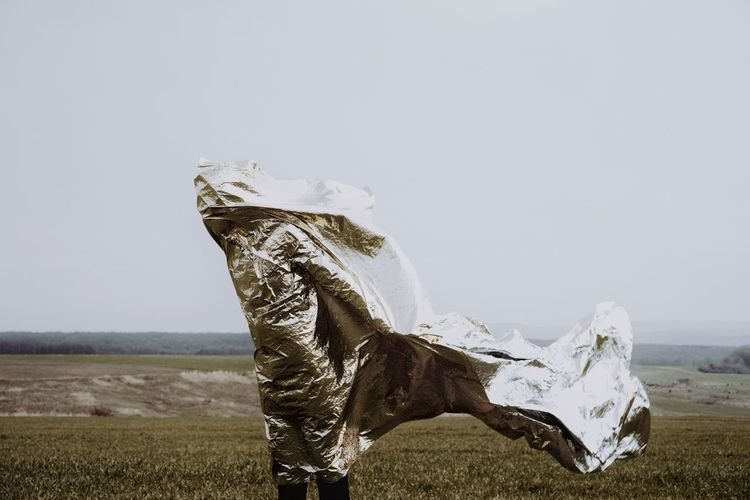 Person wrapped in textile standing on field against clear sky