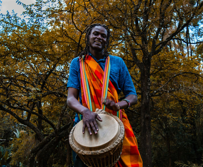 Young man with umbrella standing against trees, kenyan man doing traditional dance masai