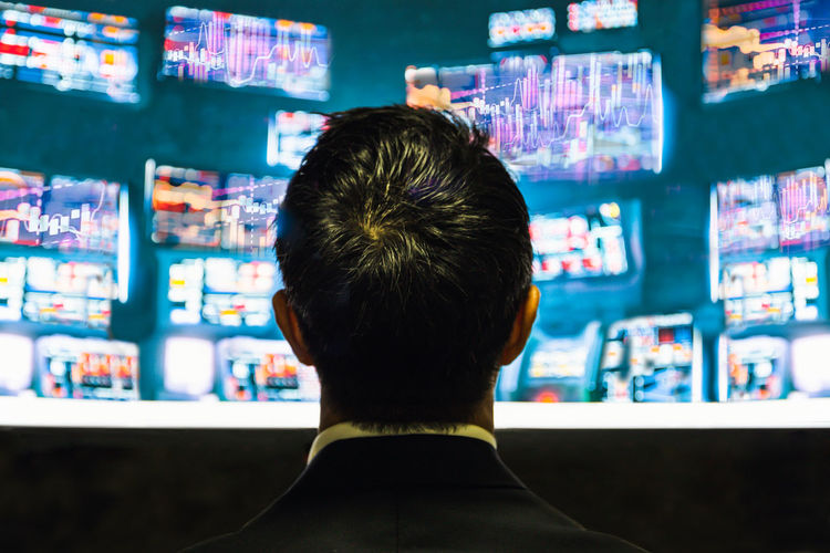 Back view of businessman trader looking at monitor with stock exchange graph