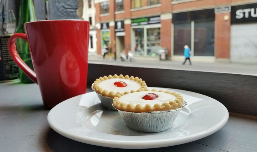 Close-Up Of Coffee With Fresh Bakewell Tarts Served In Plate At Cafe