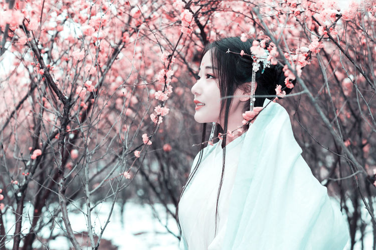 Young woman against cherry tree