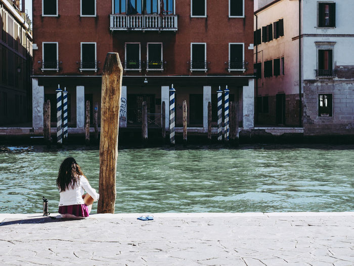 Woman sitting at canal against buildings