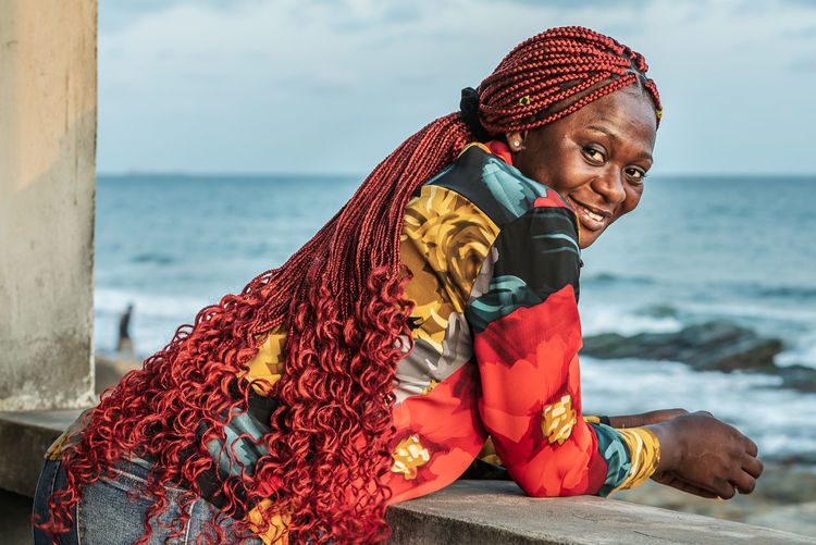 African woman with beautiful red rasta hair looking out over the sea from a balcony in accra ghana
