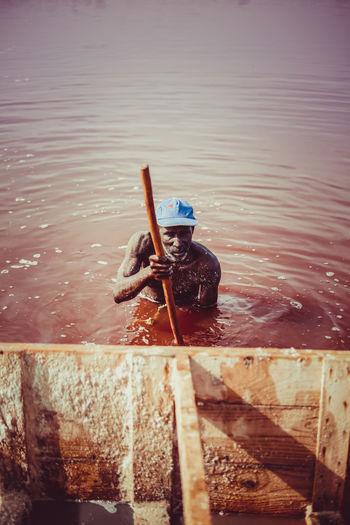 Man holding umbrella in sea