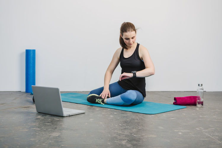 Young woman taking a break from workout in urban loft environment Wireless Technology Laptop Computer Technology Communication Connection One Person Young Adult Indoors  Using Laptop Lifestyles Real People Young Women Front View Adult Full Length Healthy Lifestyle Exercising Surfing The Net Hairstyle Fitness Workout Women Working Working Out Inside Photography Horizontal Sport Clothes Sport Clothing Athlete