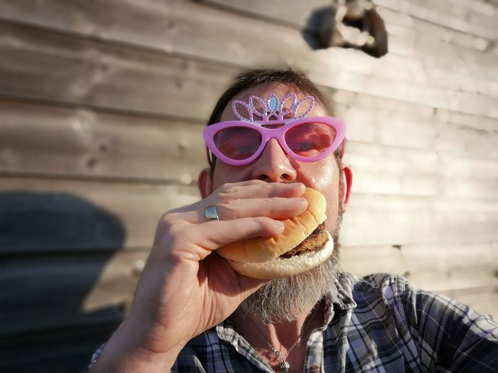 Portrait Of Man In Novelty Glasses Eating Burger Against Wall
