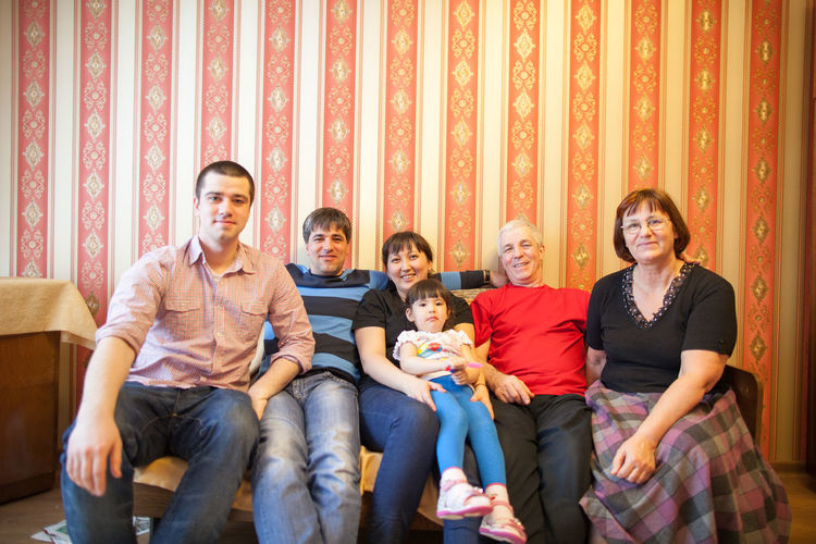Full length of happy friends sitting on sofa at home