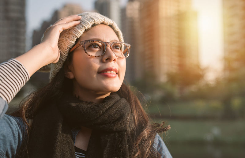Close-Up Of Young Woman Wearing Eyeglasses Against City