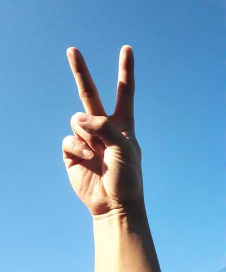 Cropped hand showing peace sign against clear blue sky