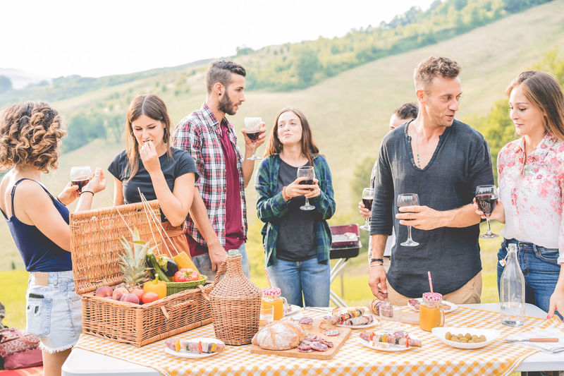 Friends enjoying drinks while standing in outdoors party