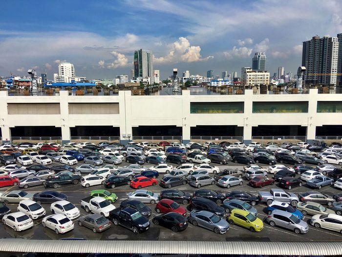 High angle view of cars at parking lot in city against sky